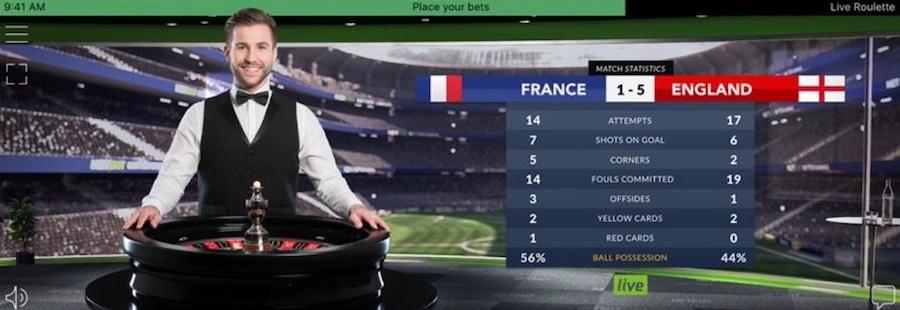 En stilig manlig croupier står framför ett roulette bord och brevid kan du se resultat från en match mellan Frankrike och England