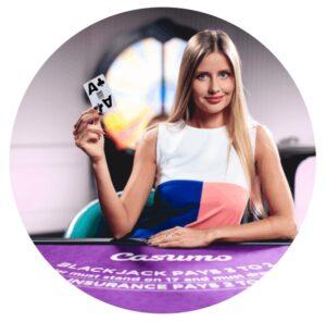 kvinnlig croupier från Casumos egna live casino studio iklädd i en lila, rosa och vit kläning. Kvinnan har långt rakt hår och håller upp två spelkort medan hon sitter vid ett blackjack-bord
