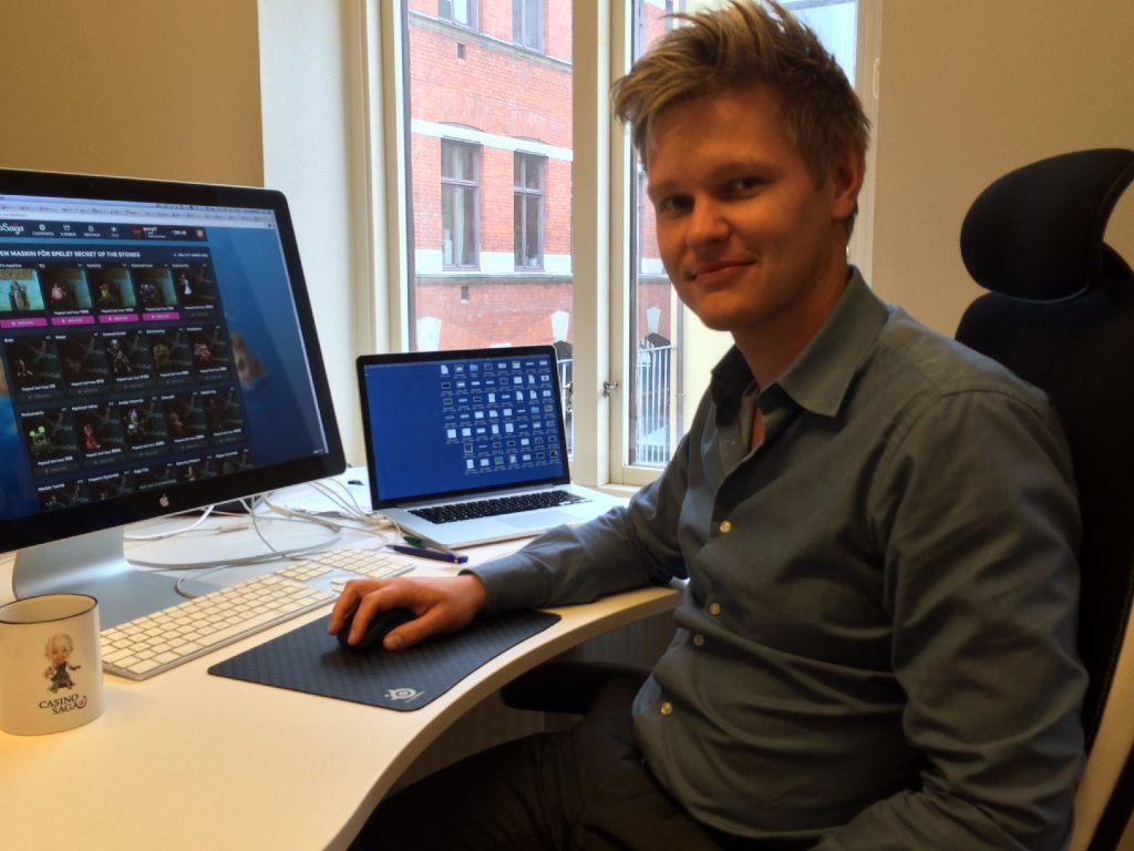 Georg Westin sitter framför två datorskärmar med ett leende på läpparna